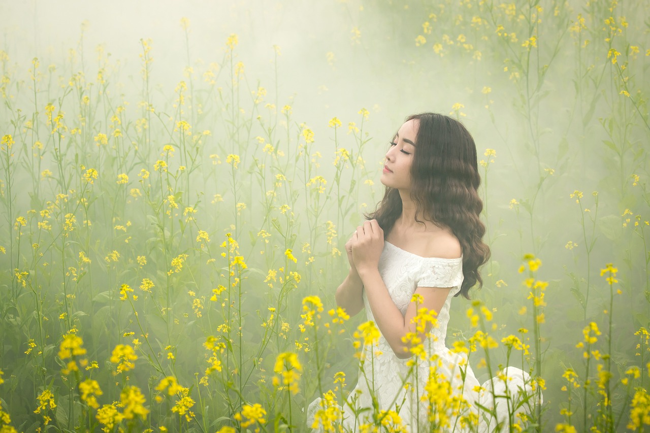 女の子が花畑で祈っている
